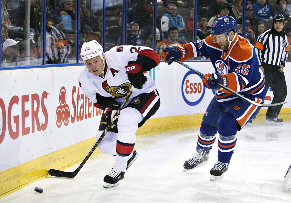 Photo - Ottawa Senators' Chris Neil, left, is chased by Edmonton Oilers' Nick Schultz (15) during the first period of an NHL hockey game, Tuesday, March 4, 2014 in Edmonton, Alberta. (AP Photo/The Canadian Press, Jason Franson)