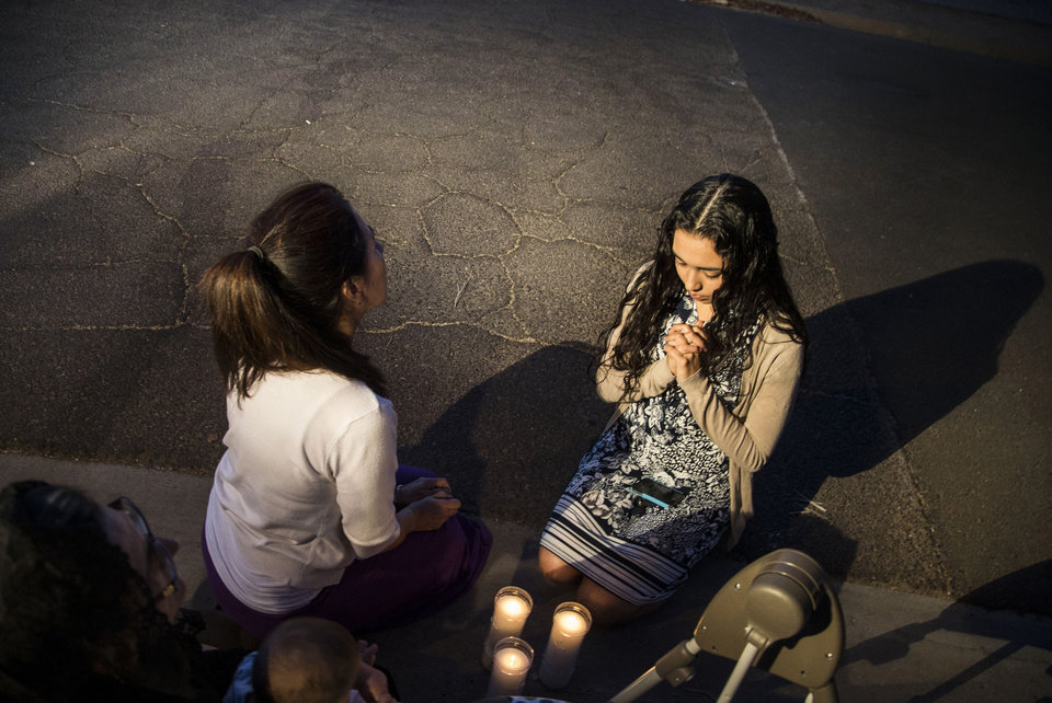 Photo - Mater Misericordiae (Mother of Mercy) Mission, church members Theresa Duarte, in center, and Kirsten Duarte, right,  pray while Phoenix Police investigate a shooting at the church on Wednesday, June 11, 2014 in Phoenix.  Police say one priest was shot to death and another is injured after an attack at the church in downtown Phoenix. The Roman Catholic Diocese of Phoenix on Thursday identified the slain priest as the Rev. Kenneth Walker and the injured priest as the Rev. Joseph Terra. (AP Photo/The Arizona Republic, Nick Oza)  MARICOPA COUNTY OUT; MAGS OUT; NO SALES