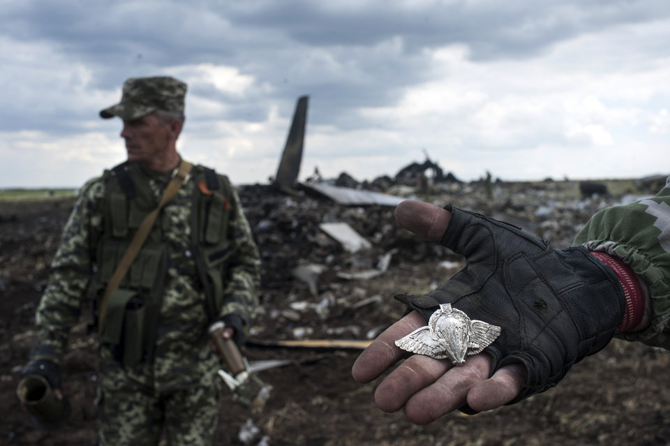 Photo - A pro-Russian fighter shows a Ukrainian paratroopers emblem as the other one carries parts of weapons form the site of remnants of a downed Ukrainian army aircraft Il-76 at the airport near Luhansk, Ukraine, Saturday, June 14, 2014. Pro-Russian separatists shot down the military transport plane Saturday in the country's restive east, killing all 49 service personnel on board, Ukrainian officials said. (AP Photo/Evgeniy Maloletka)