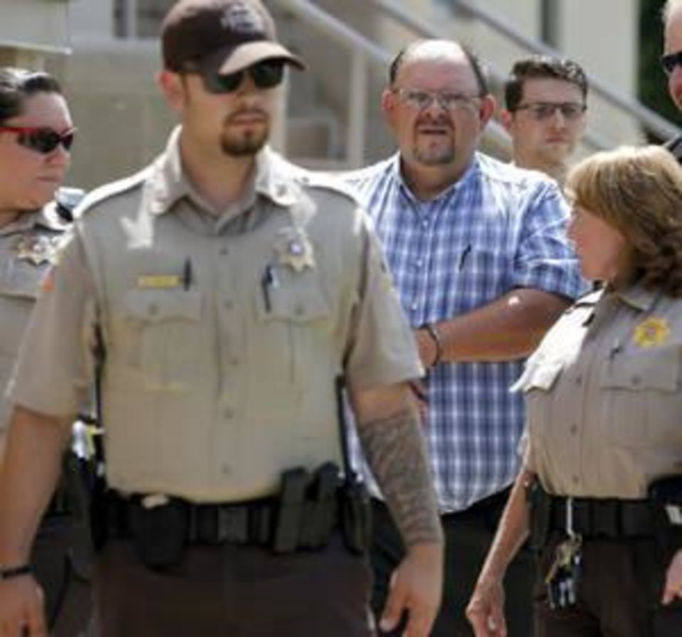 Photo -  Garfield County Sheriff Jerry Niles is led away from the Garfield County Courthouse in Enid on Tuesday after his first court appearance on a second-degree manslaughter indictment. [Photo by Bryan Terry, The Oklahoman]