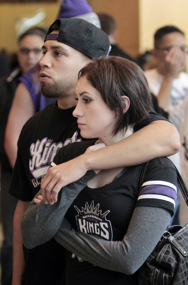 Photo - Sacramento Kings fans David Gutierrez and Maria Davila join others at City Hall for Mayor Kevin Johnson's news conference concerning the NBA basketball team, Tuesday, Jan. 22, 2013, in Sacramento, Calif. Johnson, who said he has 19 local investors who have pledged at least $1 million each to buy the franchise, made his announcement a day after the Maloof family announced it has signed an agreement to sell the Kings to a Seattle group led by investor Chris Hansen. (AP Photo/Rich Pedroncelli)
