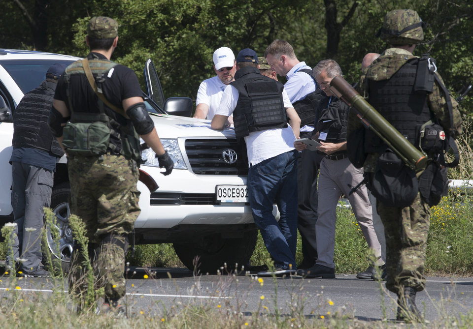 Photo - Members of the OSCE mission to Ukraine examine a map as they try to estimate security conditions outside the city of Donetsk, eastern Ukraine Wednesday, July 30, 2014. (AP Photo/Dmitry Lovetsky)