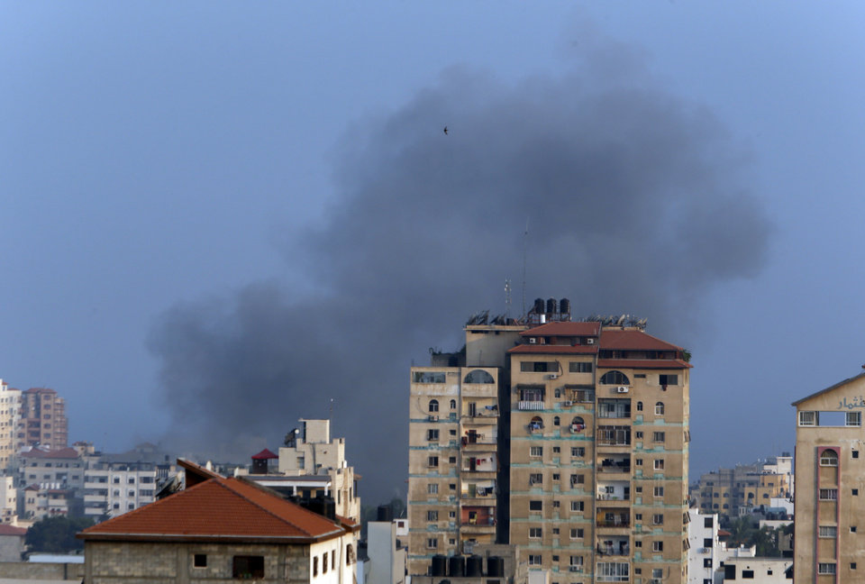 Photo - Smoke from an Israeli strike rises over Gaza City, Tuesday, July 22, 2014. A police spokesman said Israeli aircraft have hit dozens of targets in the Gaza Strip, including the home of the late leader of Hamas' military wing, several mosques and a football stadium. (AP Photo/Lefteris Pitarakis)