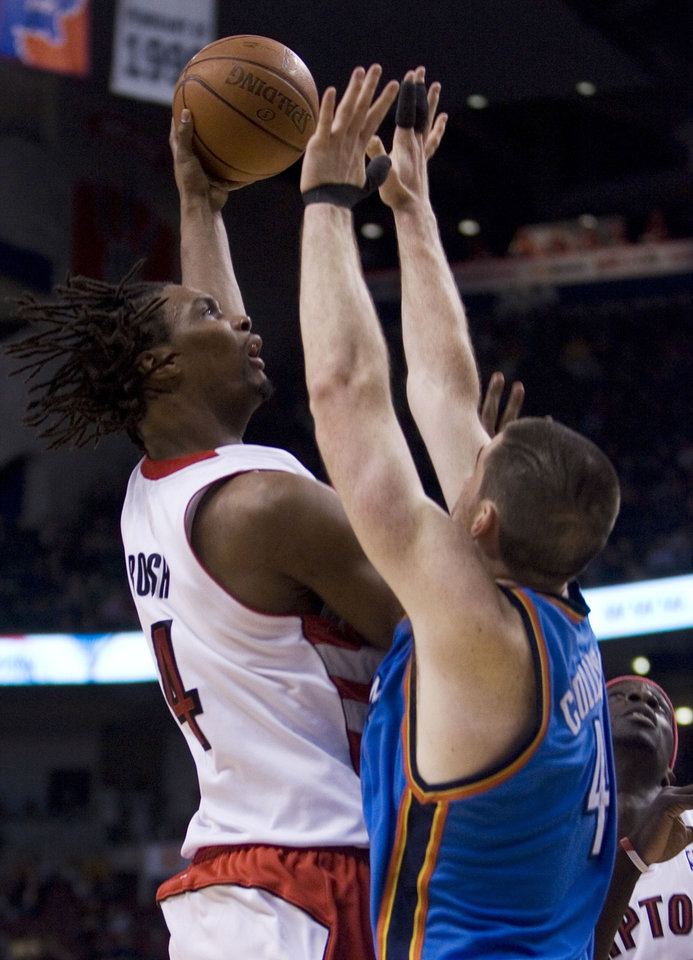 Photo - Toronto Raptors' Chris Bosh, left, scores over Oklahoma City Thunder's Nick Collison  as Raptors' Pop Mensah-Bonsu, right, looks on during first quarter NBA basketball action in Toronto, on Friday  March 27, 2009. (AP Photo/The Canadian Press, Chris Young) ORG XMIT: CFWY110