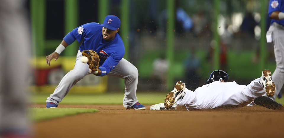 Photo - Miami Marlins' Jake Marisnick, right, steals second on a late throw from the Chicago Cubs catcher to second baseman Luis Valbuena, left, during the first inning of a baseball game in Miami, Monday, June 16, 2014. (AP Photo/J Pat Carter)
