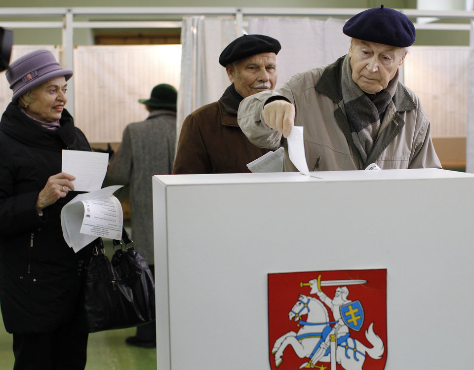 A Lithuanian voter casts his ballot at a polling station in Vilnius, Lithuania, Sunday, Oct. 14, 2012. Lithuanians are expected to deal a double-blow to the incumbent conservative government in national elections Sunday by handing a victory to opposition leftists and populists and saying \'no\' to a new nuclear power plant that supporters claim would boost the country\'s energy independence. (AP Photo/Mindaugas Kulbis)