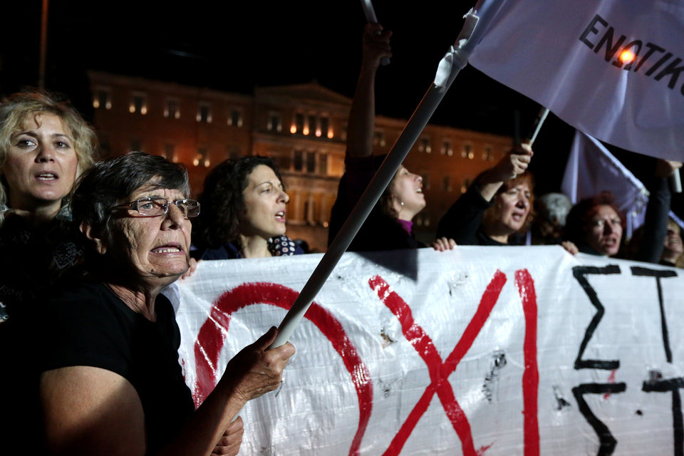 Photo - People gather outside Greece's Parliament in central Athens in support of an opposition motion of no confidence against the government, Sunday, Nov. 10, 2013. Parliament is to vote on the motion after midnight Sunday and the government is expected to hold on to its narrow majority. Banner reads
