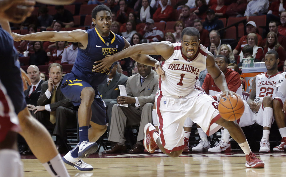 Oklahoma\'s Sam Grooms (1) drives pat West Virginia \'s Juwan Staten (3) during the first half of the college basketball game between the University of Oklahoma Sooners (OU) and the West Virginia University Mountaineers (WVU) at the Lloyd Noble Center on Wednesday, March 6, 2013, in Norman, Okla. Photo by Chris Landsberger, The Oklahoman