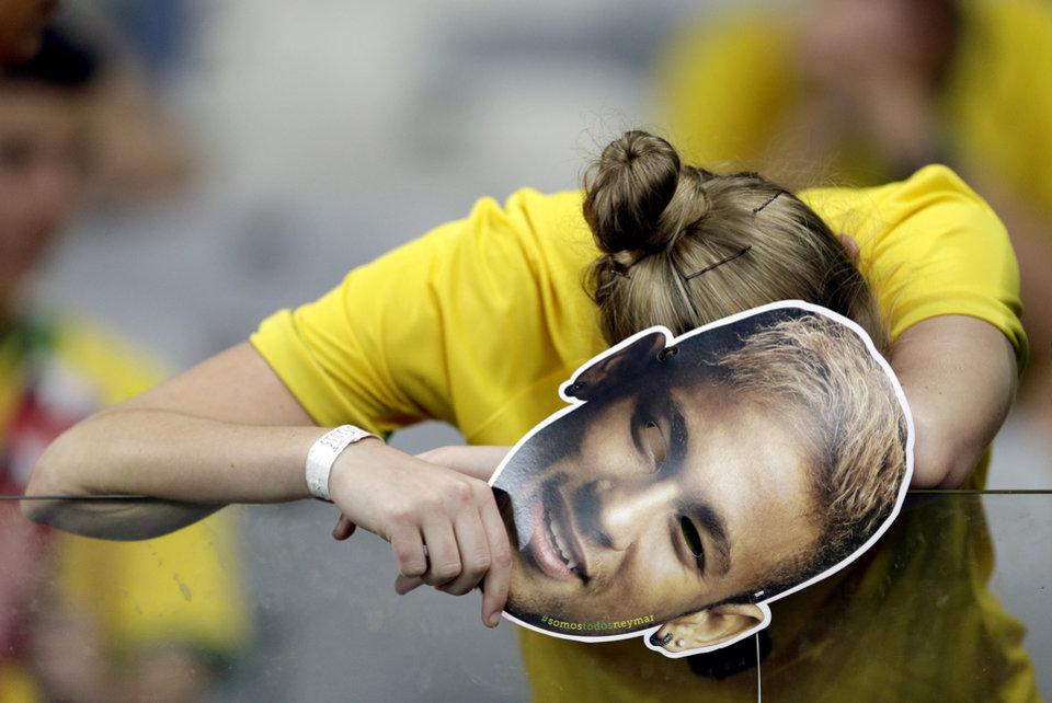 Photo - A Brazilian supporter holding a Neymar face mask reacts after Germany defeated Brazil 7-1 to advance to the finals during the World Cup semifinal soccer match between Brazil and Germany at the Mineirao Stadium in Belo Horizonte, Brazil, Tuesday, July 8, 2014. (AP Photo/Andre Penner)