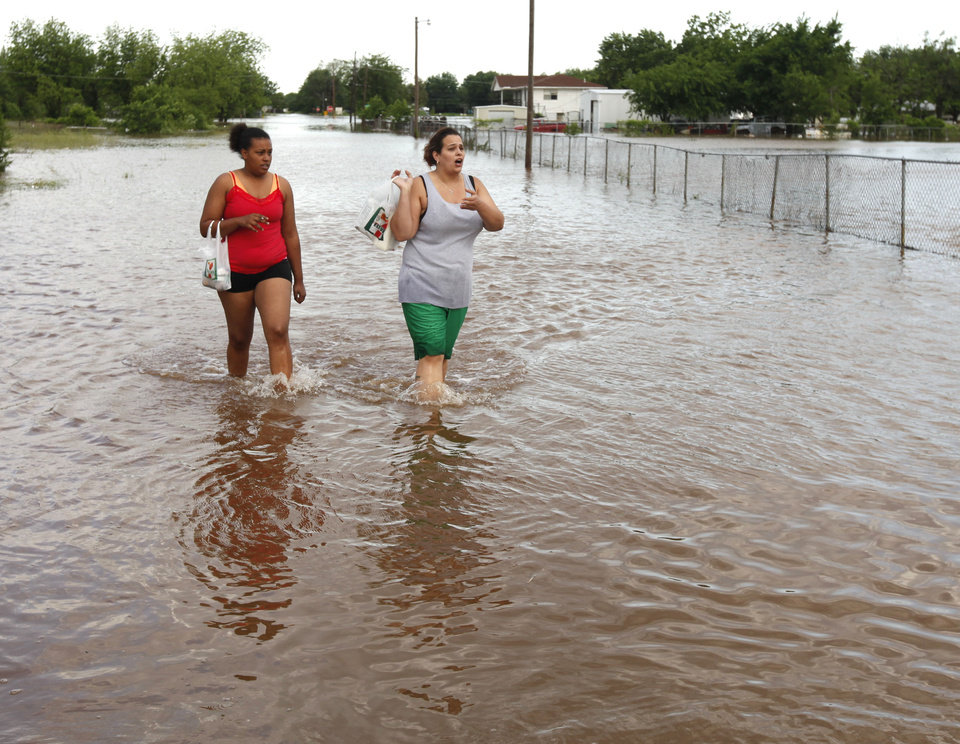 Photo - Residents walk away from a flooded mobile home park off of Air Depot Blvd. between NE 10th and NE 23rd St. in Midwest City, OK, Saturday, June 1, 2013, after up to eight inches of rain fell during the previous 24 hours. Photo by Paul Hellstern, The Oklahoman