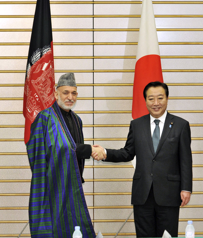 Photo -   Afghan President Hamid Karzai, left, shakes hands with Japanese Prime Minister Yoshihiko Noda prior to their talks at Noda's office in Tokyo Monday, July 9, 2012. Karzai said Monday he is encouraged by pledges to provide Afghanistan with $16 billion in aid, but warned that corruption in his country cannot be rooted out unless donors themselves take more action. (AP Photo/Yoshikazu Tsuno, Pool)