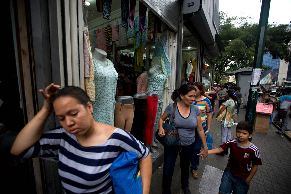Photo - People walk in front  of a shopping center that sells clothing for over weight people in downtown Caracas, Venezuela, Tuesday, Aug. 26, 2014. Venezuela's socialist government is sounding the alarm about growing waistlines in a country where record food shortages are making it harder to put healthy meals on the table, prompting many people to fill up on empty calories. (AP Photo/Fernando Llano)