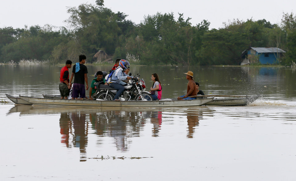 Photo - Commuters ride on a motorized boat over a rice field flooded by Typhoon Koppu in La Paz township, Tarlac province, northern Philippines Tuesday, Oct. 20, 2015. Slow-moving Typhoon Koppu blew ashore with fierce wind in the northeastern Philippines early Sunday, toppling trees and knocking out power and communications and forcing the evacuation of thousands of villagers. (AP Photo/Bullit Marquez)