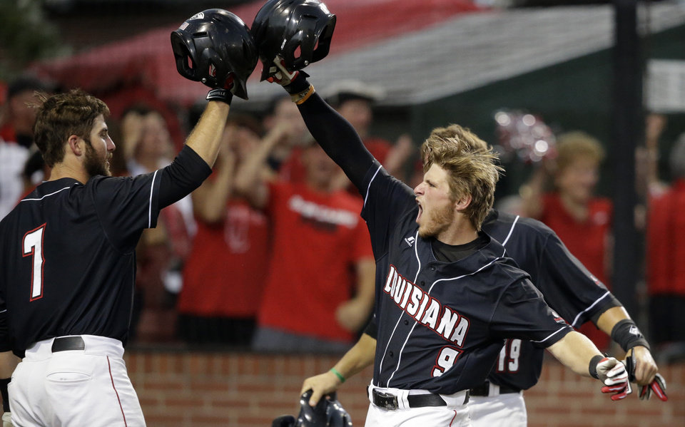 Photo - Louisiana Lafayette's Tyler Girouard (9) celebrates his three run home run with Ryan Leonards (7) and Jace Conrad (19) in the third inning of an NCAA college baseball tournament super regional game against Mississippi in Lafayette, La.,Saturday, June 7, 2014. (AP Photo/Gerald Herbert)
