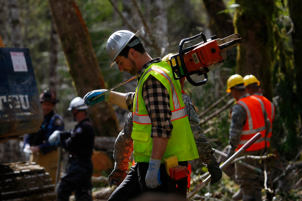 Photo - A volunteer, carrying a chainsaw, walks into the debris field, Wednesday, April 2, 2014, where workers continued to search through the mudslide area in Oso, Wash. (AP Photo/The Herald, Genna Martin)