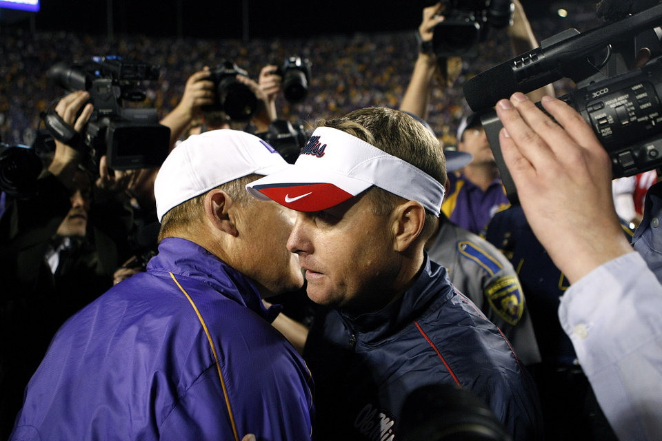 Photo -   Mississippi head coach Hugh Freeze, left, talks with LSU head coach Les Miles after their NCAA college football game in Baton Rouge, La., Saturday, Nov. 17, 2012. LSU won 41-35. (AP Photo/Gerald Herbert)
