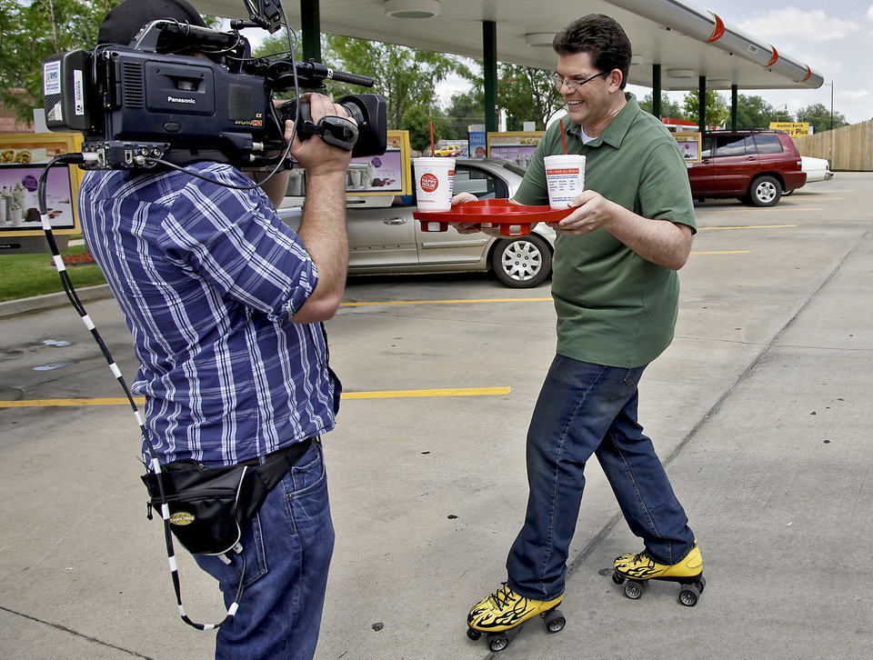 Photo - Fast Food Mania host Jon Hein tries his hand at being a car hop during a filming of the new