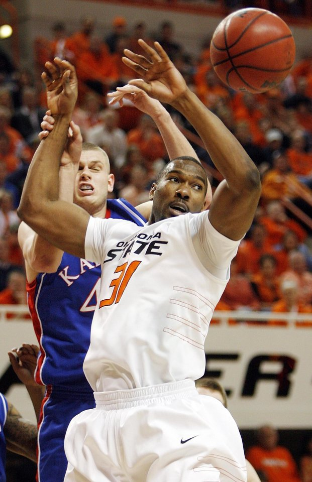 Photo - OSU's Matt Pilgrim (31) tries to rebound the ball in front of KU's Cole Aldrich (45) in the second half during the men's college basketball game between the University of Kansas (KU) and Oklahoma State University (OSU) at Gallagher-Iba Arena in Stillwater, Okla., Saturday, Feb. 27, 2010. OSU won, 85-77. Photo by Nate Billings, The Oklahoman