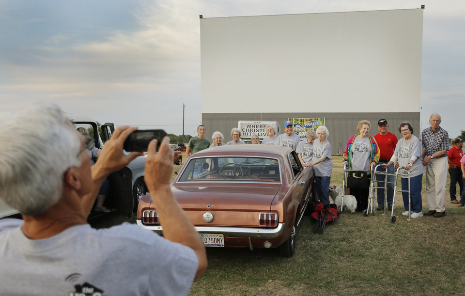 Photo - Charles Hall, whose family managed the drive-in, takes a photo of former employees before the show at the Airline Drive-in movie theater in Ponca City Thursday, August 14, 2014. Photo by Doug Hoke, The Oklahoman