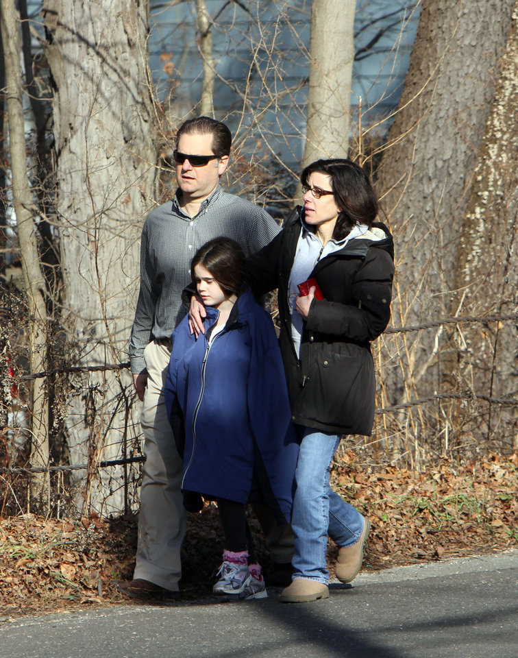 Photo - Parents walk away from the Sandy Hook Elementary School in Newtown, Conn. where authorities say a gunman opened fire, leaving 27 people dead, including 20 children, Friday, Dec. 14, 2012. (AP Photo/The Journal News, Frank Becerra Jr.) MANDATORY CREDIT, NYC OUT, NO SALES, ONLINE OUT, TV OUT, NEWSDAY INTERNET OUT; MAGS OUT ORG XMIT: NYWHI101