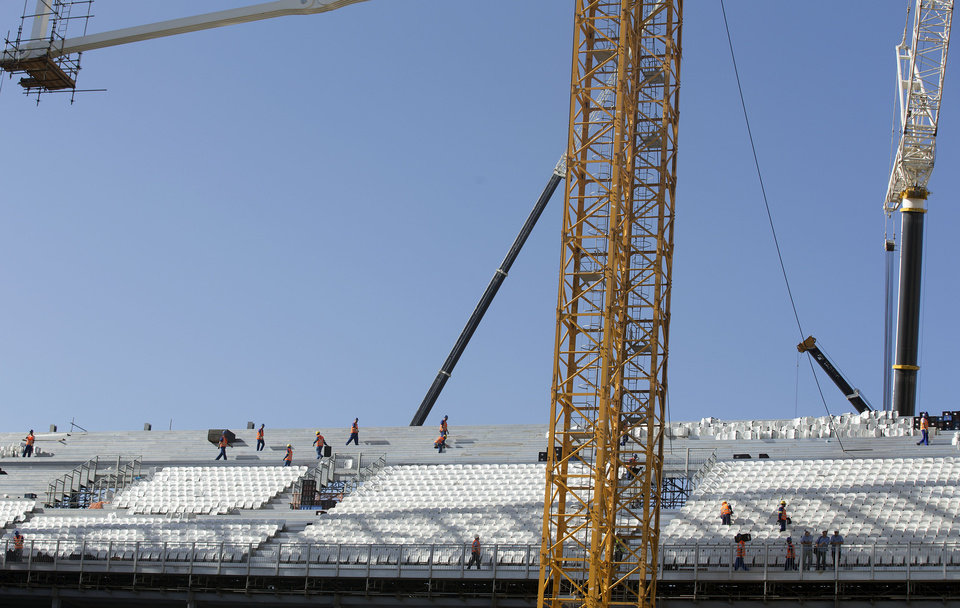 Photo - Men work at the Itaquerao, the stadium that will host the World Cup opener in less than three months in Sao Paulo, Brazil, Saturday, March 15, 2014. The Itaquerao was one of the six stadiums that were supposed to be finished by the end of 2013, but a crane collapse that killed two workers in November caused significant delays to the venue where Brazil will play Croatia on June 12. The stadium is not expected to be ready before mid-April. (AP Photo/Andre Penner)