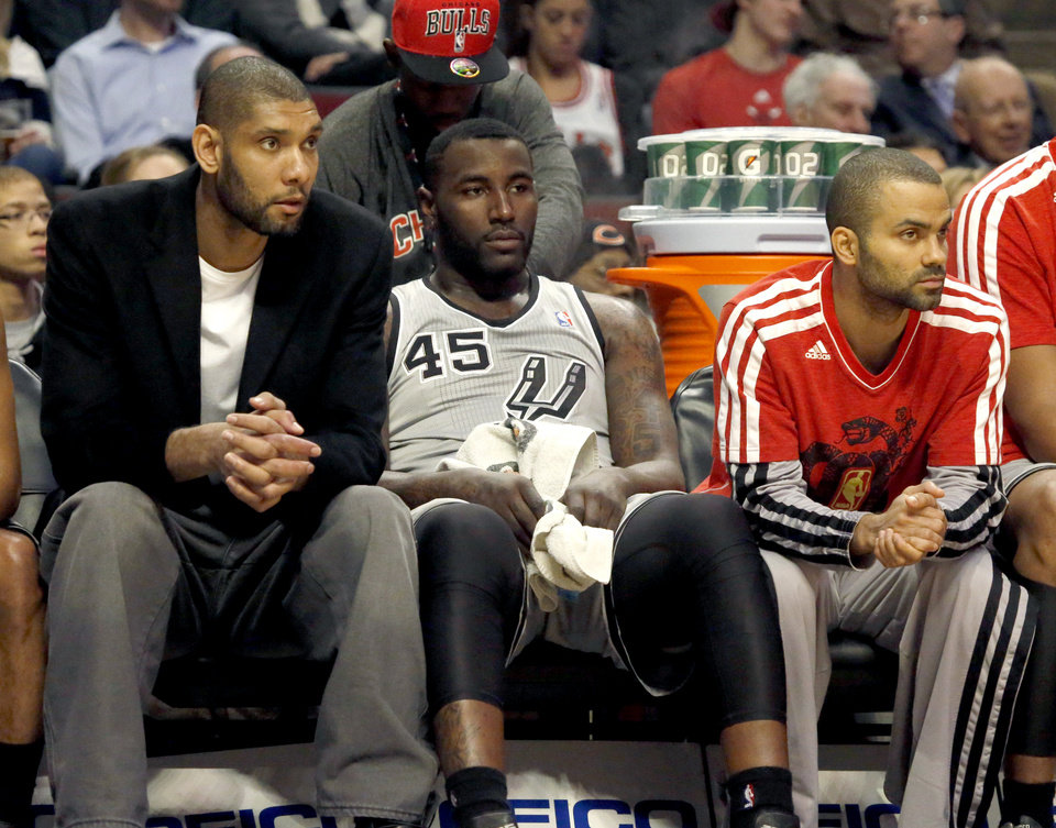San Antonio Spurs forward Tim Duncan, left, and guard Tony Parker, right, sit on the bench with DeJuan Blair (45) during the first half of an NBA basketball game against the Chicago Bulls, Monday, Feb. 11, 2013, in Chicago. (AP Photo/Charles Rex Arbogast)
