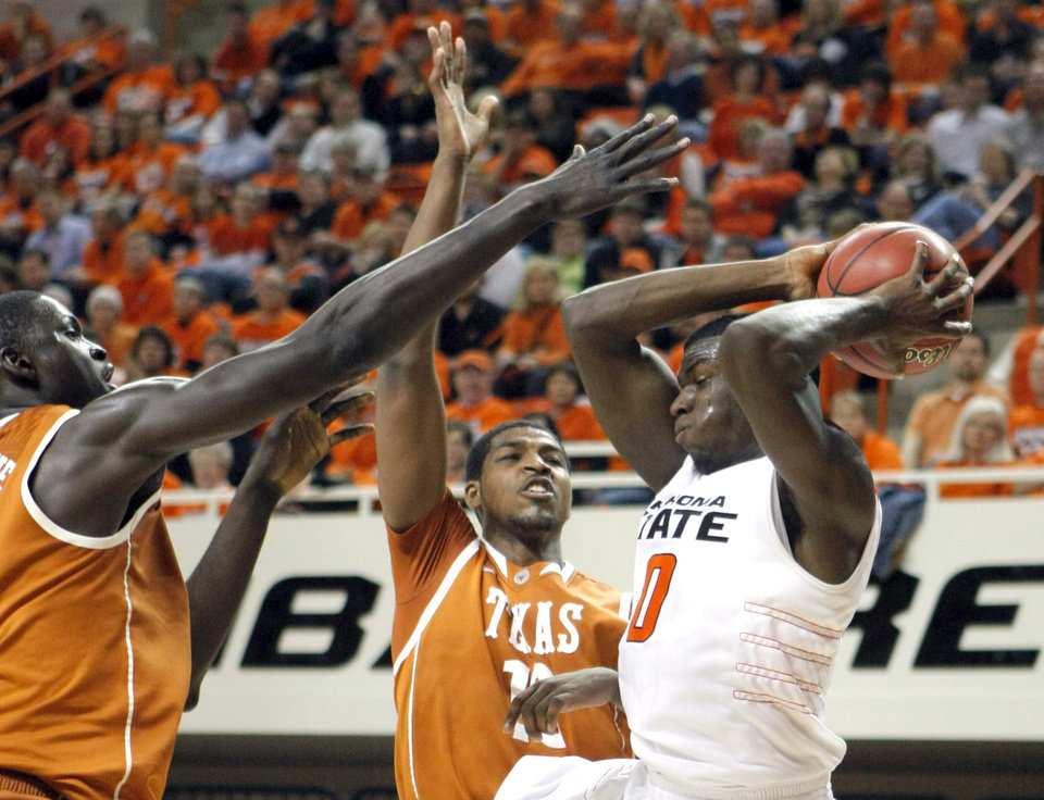Photo - Oklahoma State's Jean-Paul Olukemi (0) tries to pass the ball as he is defended by Texas' Alexis Wangmene (20) and Tristan Thompson (13) during the basketball game between Oklahoma State and Texas, Wednesday, Jan. 26, 2011, at Gallagher-Iba Arena in Stillwater, Okla. Photo by Sarah Phipps, The Oklahoman ORG XMIT: KOD