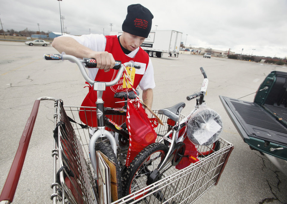 Volunteer Lariat Stewart, from Seminole, loading bikes into a vehicle as parents and guardians pick up Angel Tree gifts at the Salvation Army Christmas Center in Midwest City Tuesday, Dec. 20, 2011. Photo by Paul B. Southerland, The Oklahoman ORG XMIT: KOD
