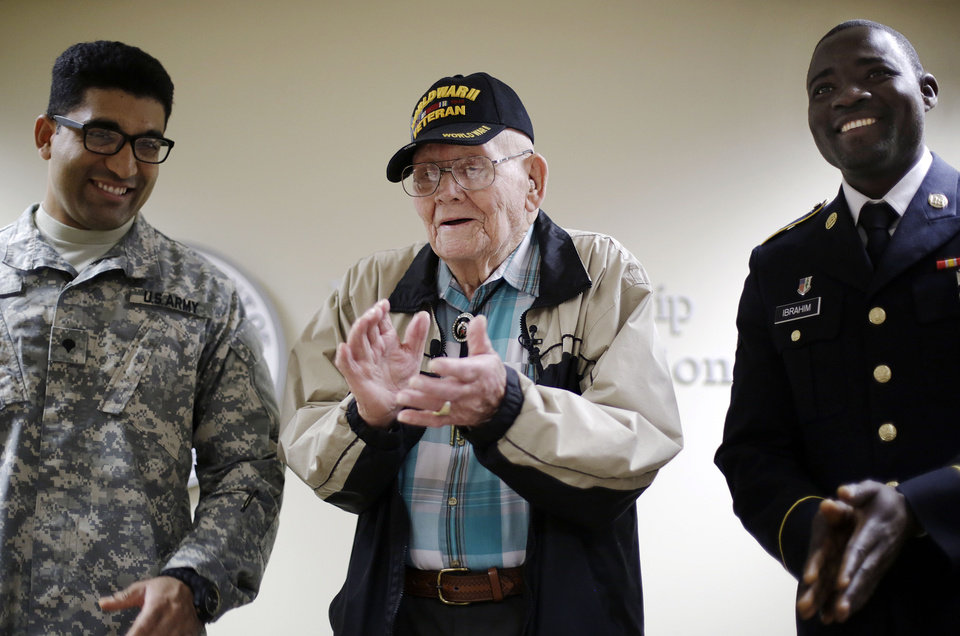 Photo - Ninety-four-year-old World War II veteran Sherwin Callander, center, applauds after a naturalization ceremony with U.S. Army Spc. Gulam Ali, left, originally from India, and U.S. Army Spc. Iddrisu Ibrahim, originally from Ghana, right, Monday, June 2, 2014, in Atlanta. The World War II veteran from Alabama is headed to France for D-Day ceremonies, a trip that seemed unlikely just last week. Callander read about ceremonies for the 70th anniversary of D-Day and thought it would be meaningful to go. He hadn't been back to France since landing on Utah Beach during the Battle of Normandy, but he hit a snag when he went to get a passport. Callander was born in Canada to an American mother, and his family moved to the U.S. when he was 3. But he didn't have documentation proving his U.S. citizenship. Federal officials heard his story and on Monday gave him a proof of citizenship certificate so he could get a passport in time to leave for France just hours later. (AP Photo/David Goldman)