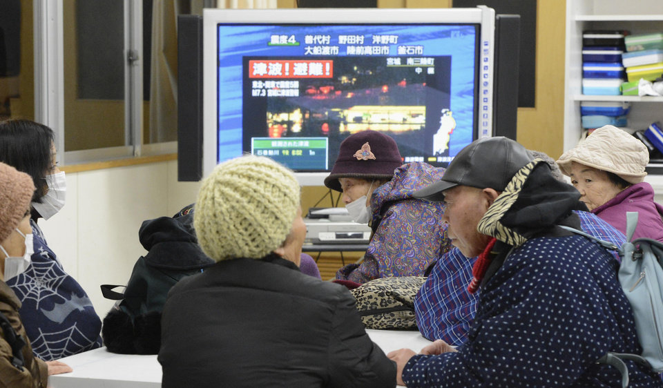 Photo - Tsunami evacuees watch TV news flashing a tsunami warning at their shelter Takata Junior High School that stands on a higher ground in Rikuzentakata in Iwate Prefecture, Friday, Dec. 7, 2012 after a strong earthquake struck off the coast of northeastern Japan. It is the same region that was hit by a massive earthquake and tsunami last year. (AP Photo/Kyodo News) JAPAN OUT, MANDATORY CREDIT, NO LICENSING IN CHINA, FRANCE, HONG KONG, JAPAN AND SOUTH KOREA