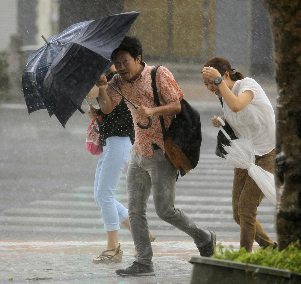 Photo - People hold umbrellas through heavy rain caused by a typhoon in Naha, Okinawa, Wednesday, July 9, 2014. A powerful storm slammed through the southwestern Japanese island of Okinawa, leaving at least 28 people injured and 63,000 homes without power before swerving toward the bigger island of Kyushu on Wednesday. (AP Photo/Kyodo News) JAPAN OUT, MANDATORY CREDIT