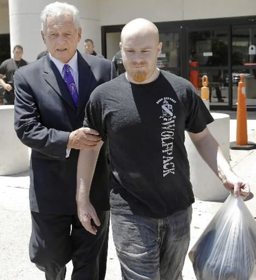 Photo - Attorney Irven Box, left, walks with Justin Adams after Adams was released July 25 on $100,000 bond from the Oklahoma County jail in Oklahoma City. Photo by Chris Landsberger, The Oklahoman Archvies     ORG XMIT: 1301092221078466
