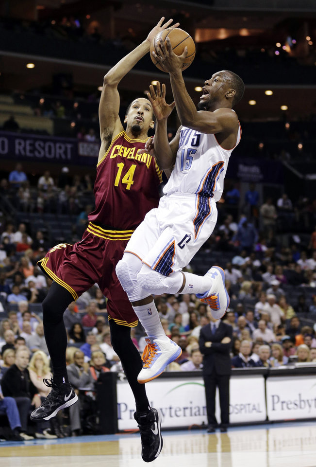 Photo - Charlotte Bobcats' Kemba Walker (15) drives past Cleveland Cavaliers' Shaun Livingston (14) during the first half of an NBA basketball game in Charlotte, N.C., Wednesday, April 17, 2013. (AP Photo/Chuck Burton)
