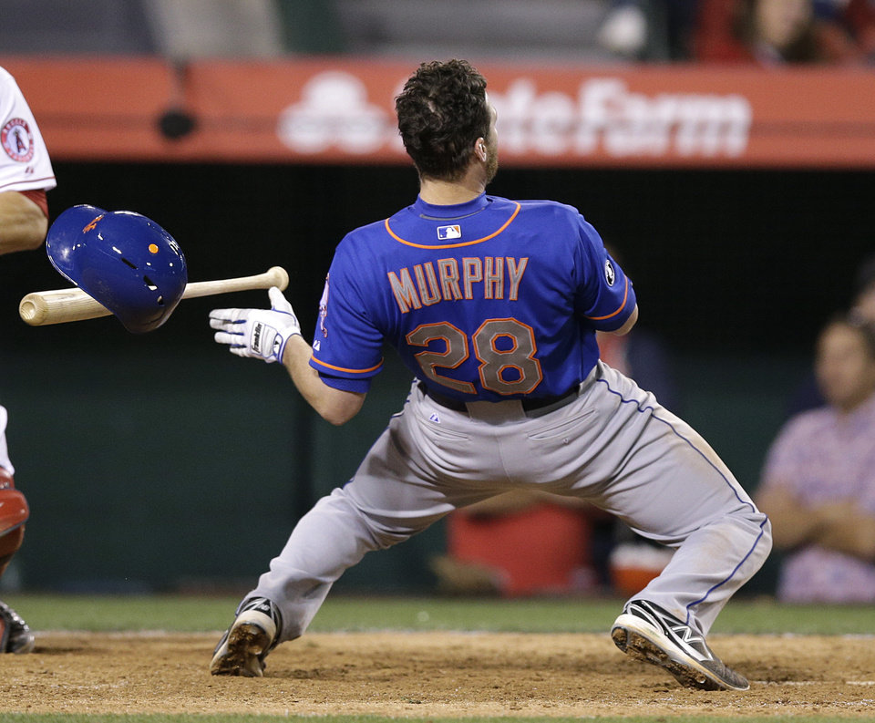 Photo - New York Mets' Daniel Murphy looses his helmet as he avoids a pitch during the 13th inning of a baseball game against the Los Angeles Angels on Saturday, April 12, 2014, in Anaheim, Calif. (AP Photo/Jae C. Hong)