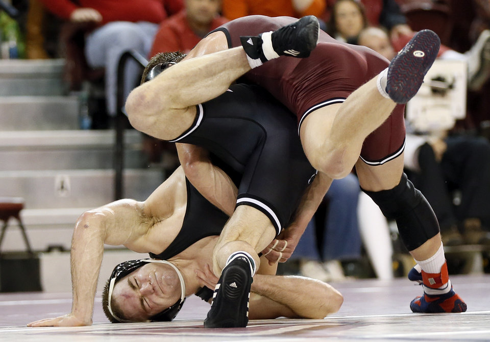Photo - OSU's Chris Perry, bottom, and OU's Andrew Howe wrestle in the 174-pound weight class during the Bedlam wrestling dual between the Oklahoma State Cowboys and the Oklahoma Sooners at McCasland Field House in Norman, Okla., Sunday, Dec. 1, 2013. OU won the dual, 16-15. Photo by Nate Billings, The Oklahoman