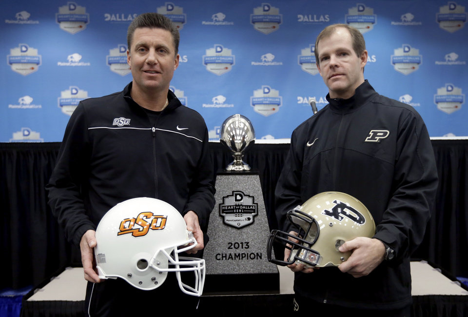 Photo - Oklahoma State head coach Mike Gundy, left, and Purdue head coach Patrick Higgins, right, pose for photos following a news conference for the Heart of Dallas Bowl NCAA college football game, Monday, Dec. 31, 2012, in Dallas. Oklahoma State is scheduled to play Purdue Tuesday. (AP Photo/Tony Gutierrez) ORG XMIT: TXTG112