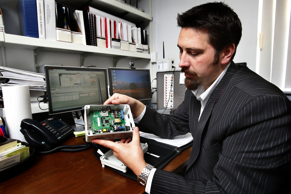 Photo - University of Oklahoma Utility Systems Analyst shows a radio data transfer unit that will be used to gather energy efficiency data on the Norman campus on Tuesday, Nov. 27, 2012 in Norman, Okla.  Photo by Steve Sisney