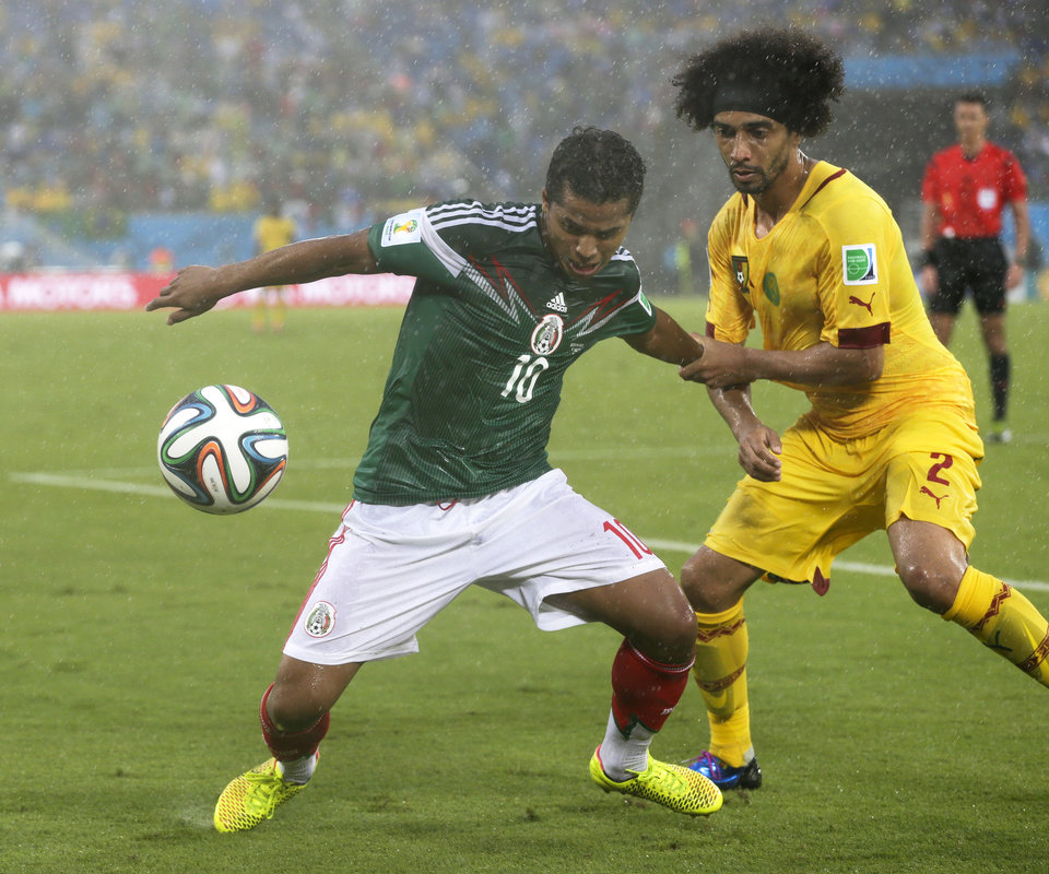 Photo - Cameroon's Benoit Assou-Ekotto (2) tries to pull Mexico's Giovani dos Santos (10) away from the ball during the second half of the group A World Cup soccer match between Mexico and Cameroon in the Arena das Dunas in Natal, Brazil, Friday, June 13, 2014.  (AP Photo/Petr David Josek)