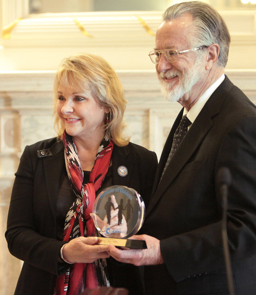 Gov. Mary Fallin receives an award from Doug Gibson, executive director of the Institute for Child Advocacy. Photo By David McDaniel, The Oklahoman