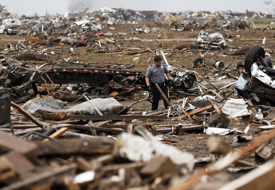 A police officer searches through debris just east of Western and north of SW 149th after a tornado struck south Oklahoma City and Moore, Okla., Monday, May 20, 2013. Photo by Nate Billings, The Oklahoman