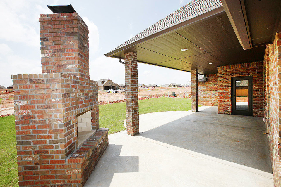 Photo - The outdoor fireplace makes the covered patio a real outdoor living area at R&R Homes' project house for the Moore Home Builders Association as part of the Southwest Showcase of Homes.  David McDaniel - The Oklahoman
