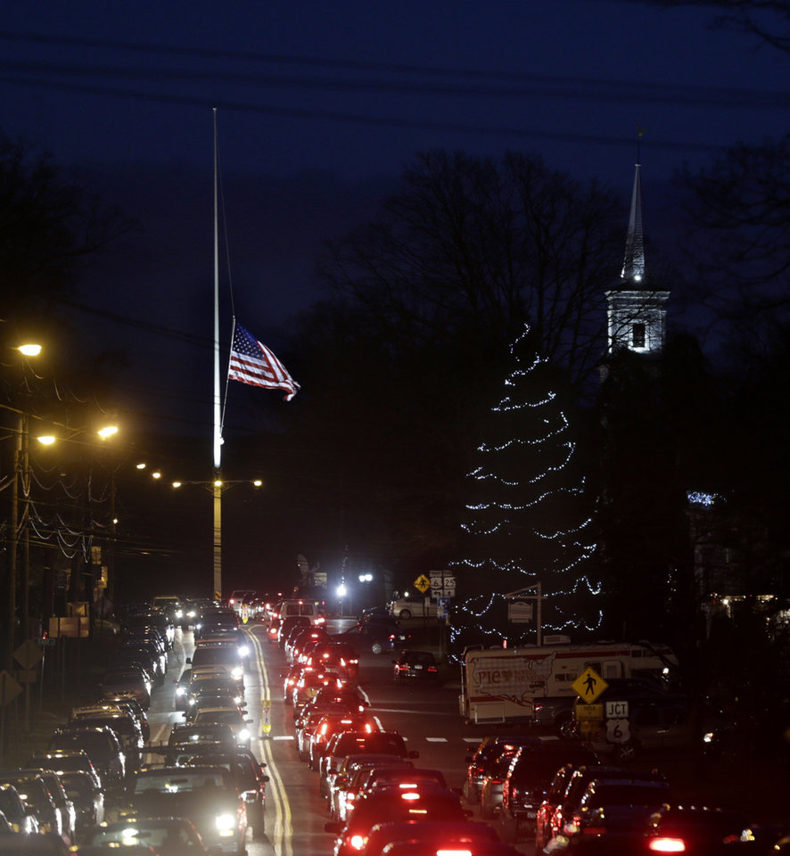 Under a flag at half-staff and a Christmas tree, traffic piles up along a main road in Newtown, Conn., Thursday, Dec. 20, 2012. (AP Photo/Seth Wenig)
