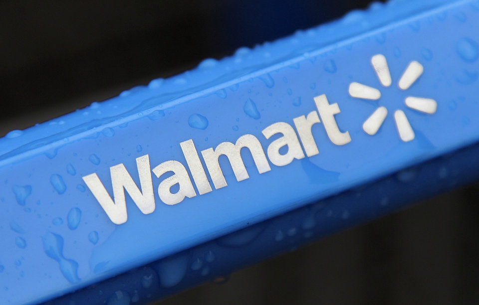 FILE - This Nov. 14, 2011 file photo shows the rain-soaked handle of a shopping cart outside the Walmart store in Mayfield Heights, Ohio. Wal-Mart Stores Inc. will be testing this summer an option for consumers to be able to order product on its website and then have it kept in a physical locker at the store so they can pick it up without having to wait in line or talk to a store clerk. (AP Photo/Amy Sancetta, File)