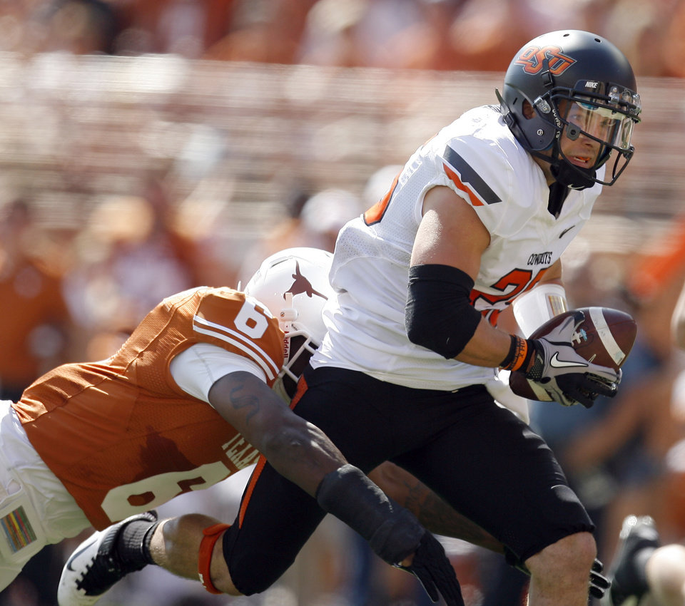 Oklahoma State's Josh Cooper (25) is brought down by Texas' Christian Scott (6) during first half of a college football game between the Oklahoma State University Cowboys (OSU) and the University of Texas Longhorns (UT) at Darrell K Royal-Texas Memorial Stadium in Austin, Texas, Saturday, Oct. 15, 2011. Photo by Sarah Phipps, The Oklahoman
