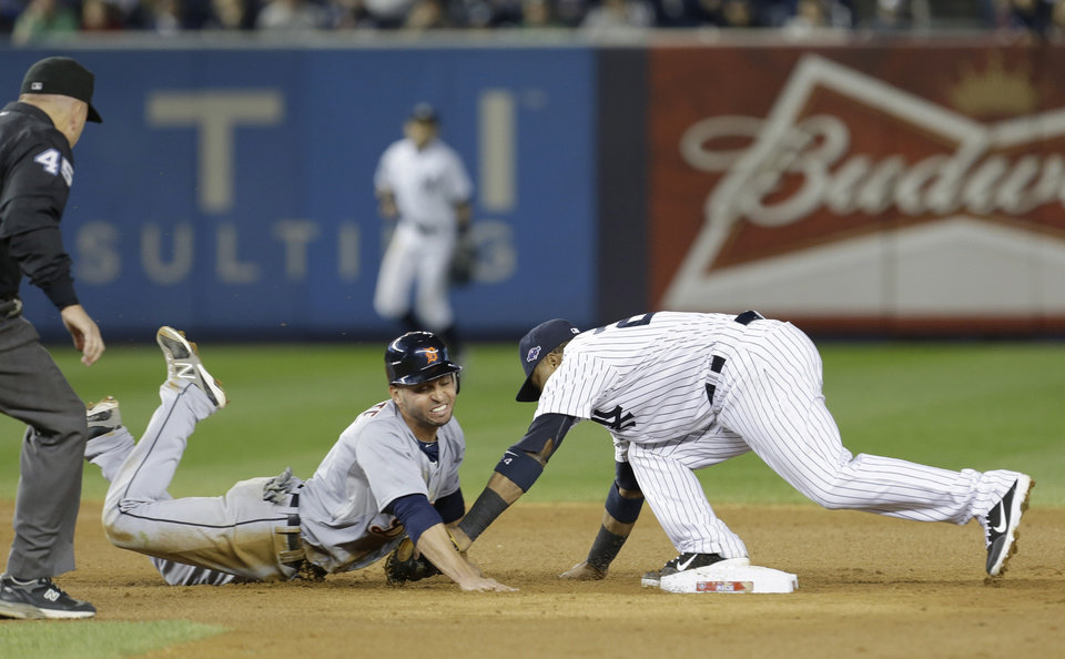 Photo -   Detroit Tigers' Omar Infante dives back into second as New York Yankees' Robinson Cano reaches to tag him in the eighth inning of Game 2 of the American League championship series Sunday, Oct. 14, 2012, in New York. Infante was called safe on the play by umpire Jeff Nelson. (AP Photo/Paul Sancya )