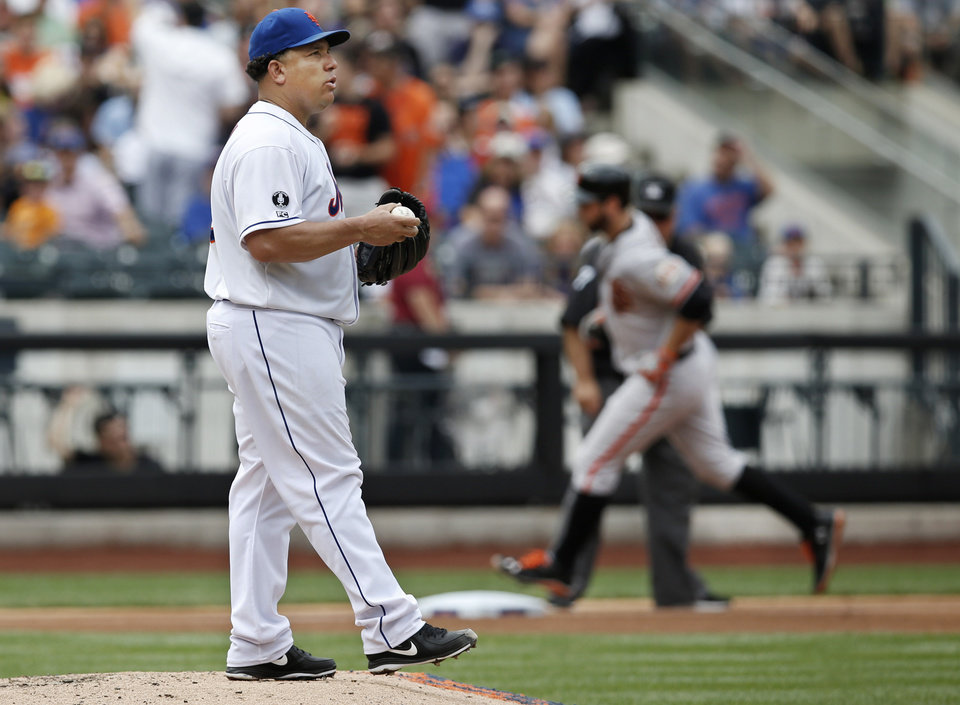 Photo - New York Mets starting pitcher Bartolo Colon (40) looks toward the outfield as San Francisco Giants' Brandon Belt trots past him after Belt hit a fourth-inning, solo home run off Colon in a baseball game in New York, Sunday, Aug. 3, 2014. (AP Photo/Kathy Willens)
