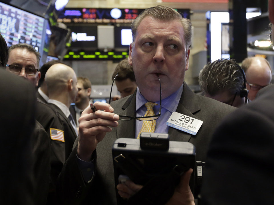 Photo - Trader Mathias Roberts works on the floor of the New York Stock Exchange Friday, Jan. 31, 2014. Stocks fell sharply in early trading Friday, as investors fretted over disappointing earnings from companies like Amazon.com and more trouble in overseas markets. (AP Photo/Richard Drew)