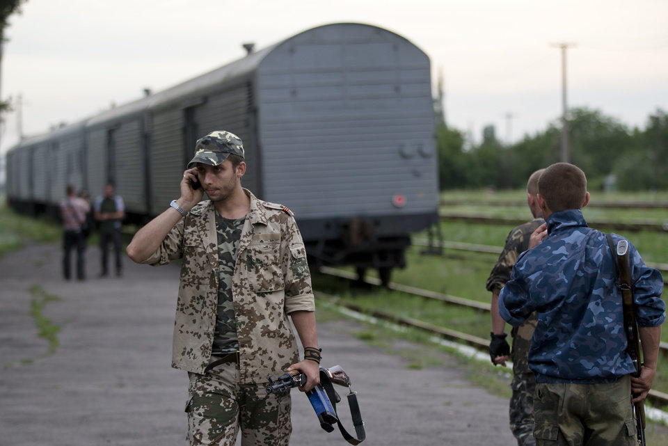 Photo - A pro-Russian rebel speaks on the phone as a refrigerated train loaded with bodies of the passengers departs the station in Torez, eastern Ukraine, 15 kilometers (9 miles) from  the crash site of Malaysia Airlines Flight 17, Monday, July 21, 2014. Another 21 bodies have been found in the sprawling fields of east Ukraine where Malaysia Airlines Flight 17 was downed last week, killing all 298 people aboard. International indignation over the incident has grown as investigators still only have limited access to the crash site and it remains unclear when and where the victims' bodies will be transported. (AP Photo/Vadim Ghirda)