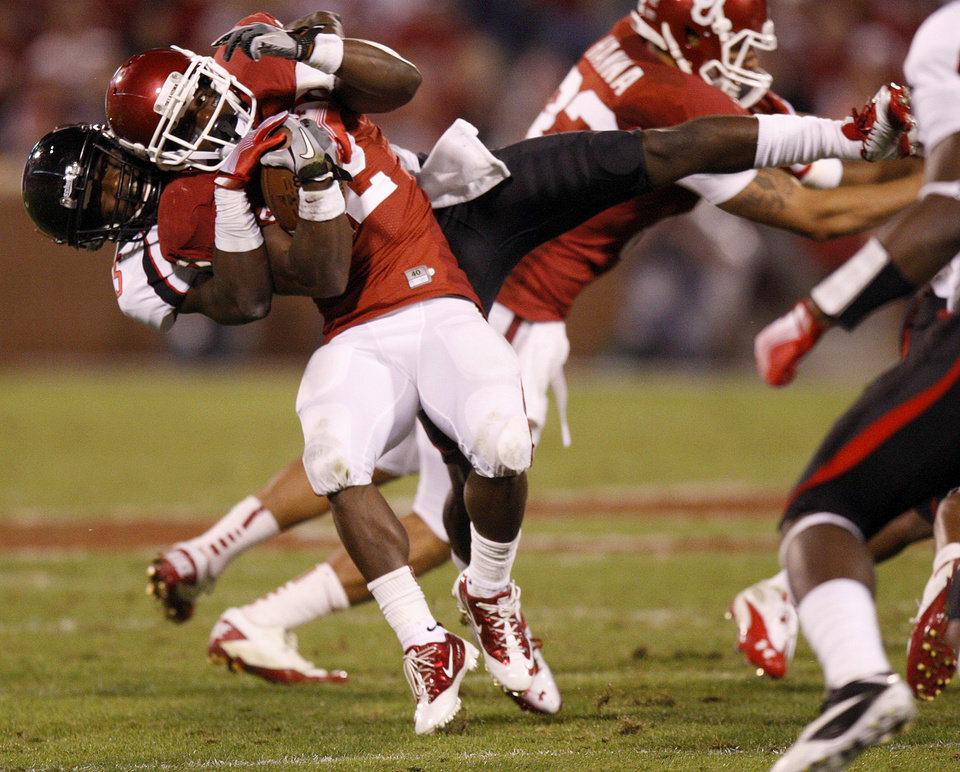 Photo - Oklahoma's Roy Finch (22) is brought down by Texas Tech's Tre' Porter (5) during the college football game between the University of Oklahoma Sooners (OU) and the Texas Tech University Red Raiders (TTU) at Gaylord Family-Oklahoma Memorial Stadium in Norman, Okla., Saturday, Oct. 22, 2011. Photo by Bryan Terry, The Oklahoman