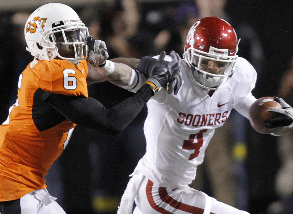 Photo - Oklahoma's Kenny Stills (4) stiff arms Oklahoma State's Andrew McGee (6) after a reception during the Bedlam college football game between the University of Oklahoma Sooners (OU) and the Oklahoma State University Cowboys (OSU) at Boone Pickens Stadium in Stillwater, Okla., Saturday, Nov. 27, 2010. Photo by Chris Landsberger, The Oklahoman